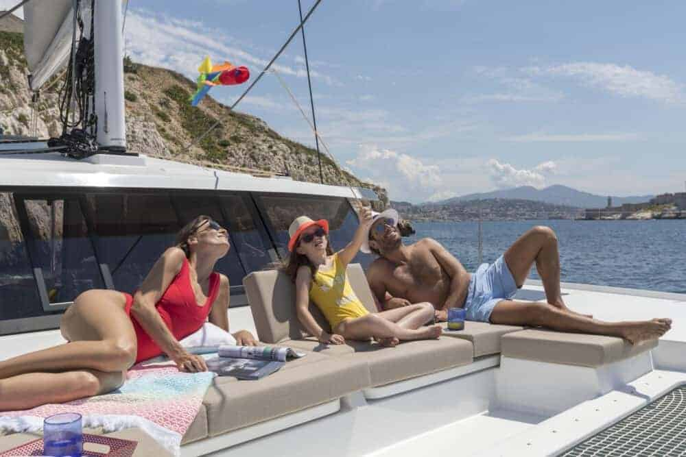 Family of 3 enjoying the sun on the massive front dek of the Beautiful and luxurious design of the spacious head of the Fountaine Pajot Astrea 42