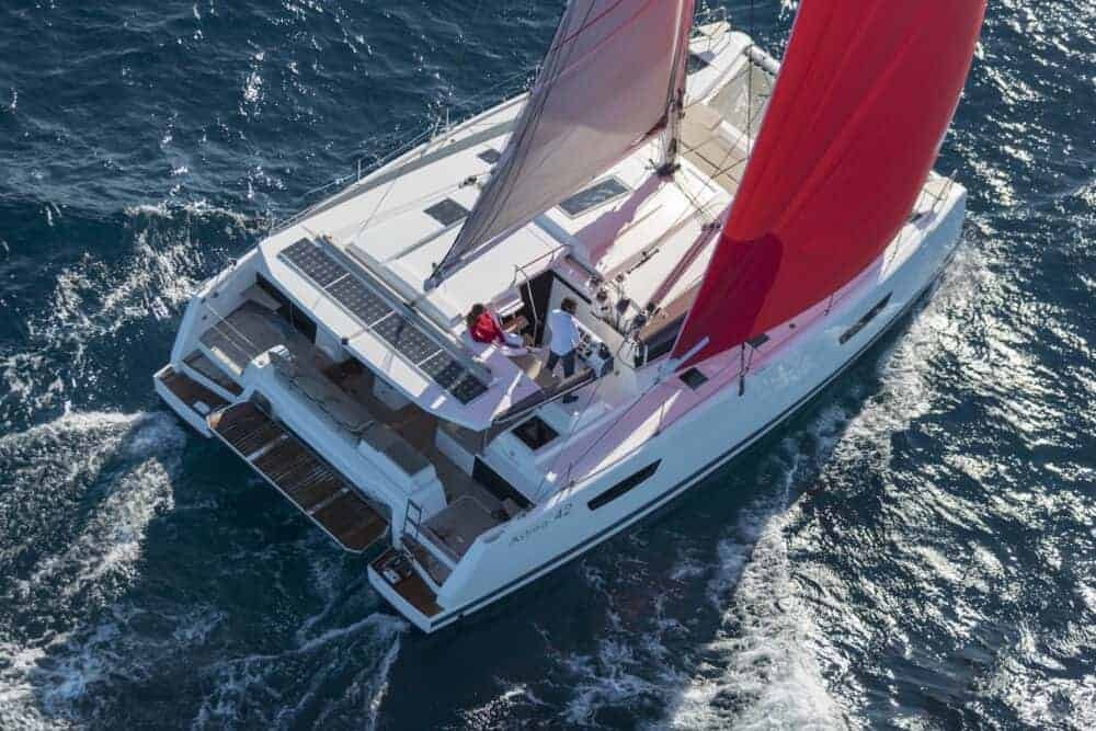 Couple sailing the Beautiful and luxurious design of the spacious head of the Fountaine Pajot Astrea 42 through the crashing waves