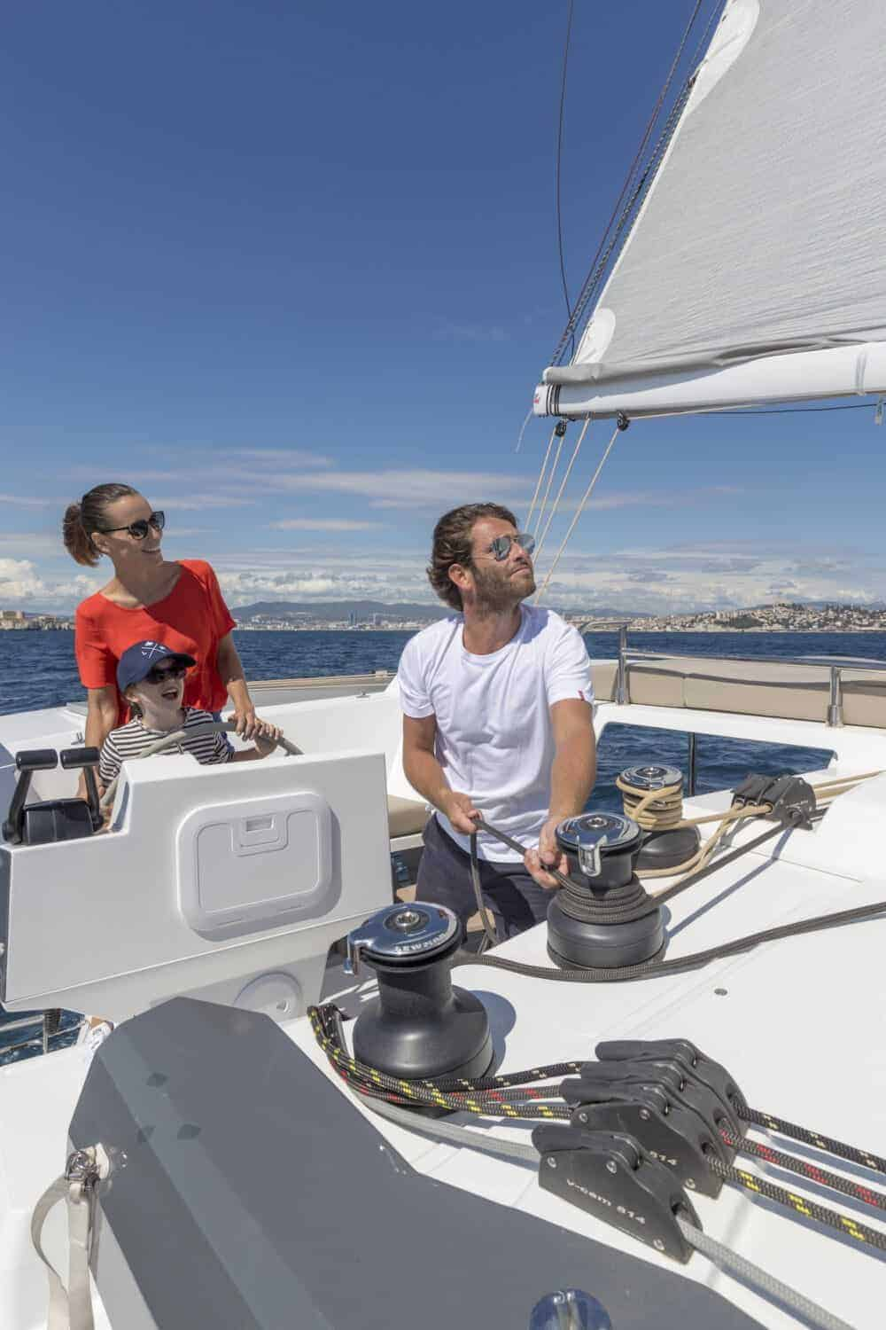 family of 3 laughing while crusing with their Beautiful and luxurious design of the spacious head of the Fountaine Pajot Astrea 42