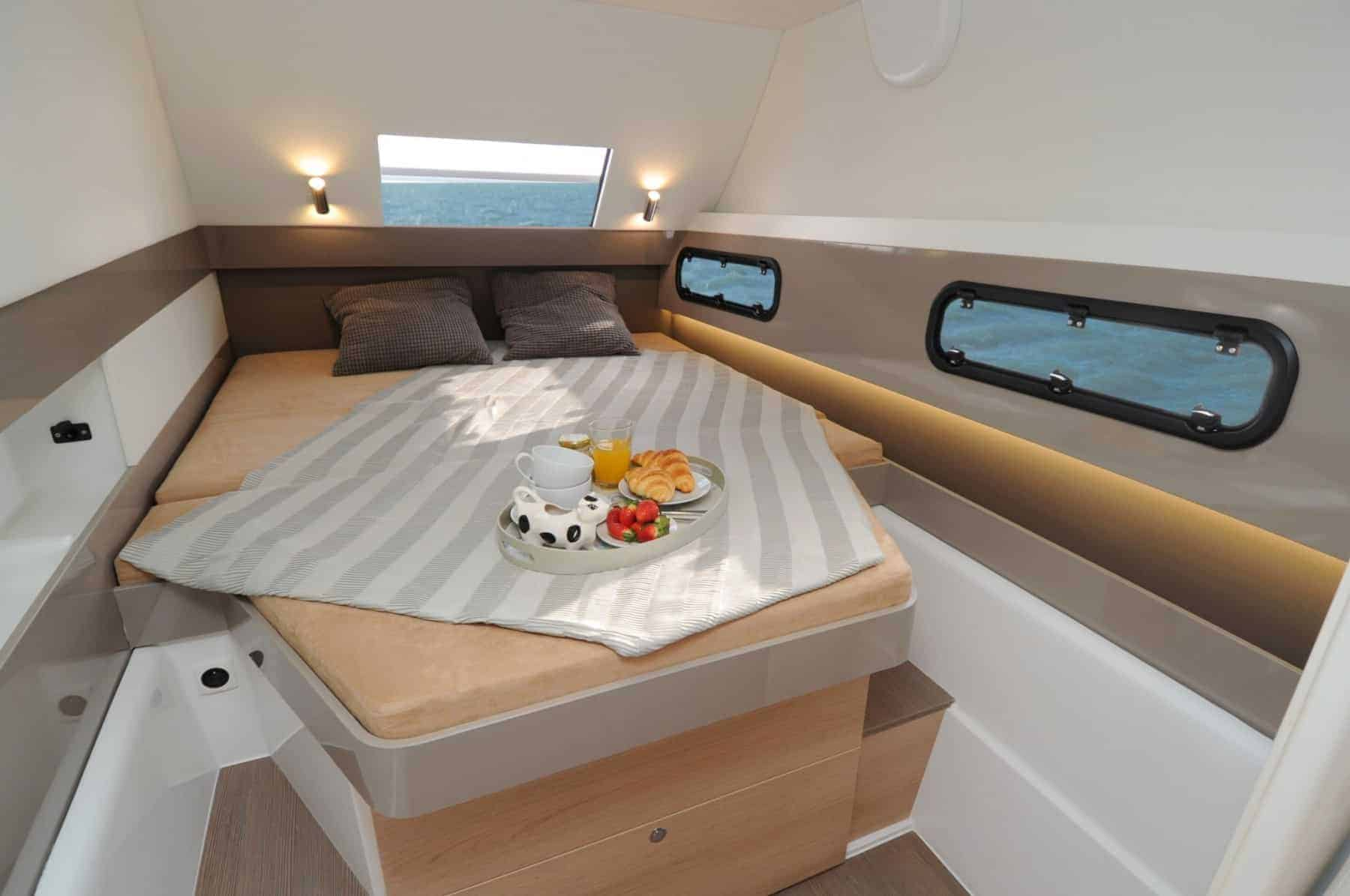 Made bed with breakfast on a plate on it in a Bali 4.1's cabin