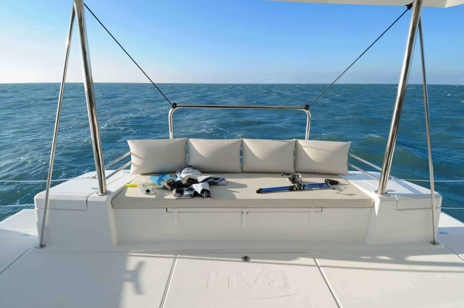 A beige couch on the Bali 4.1 catamaran's cockpit with diving equipment on it