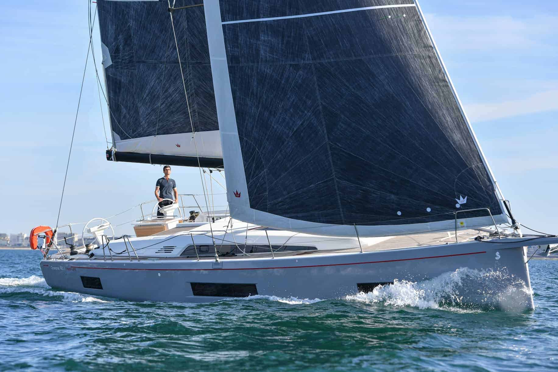 The majestic Beneteau Oceanis 46.1 in action with wind in its sail and a man at the cockpit