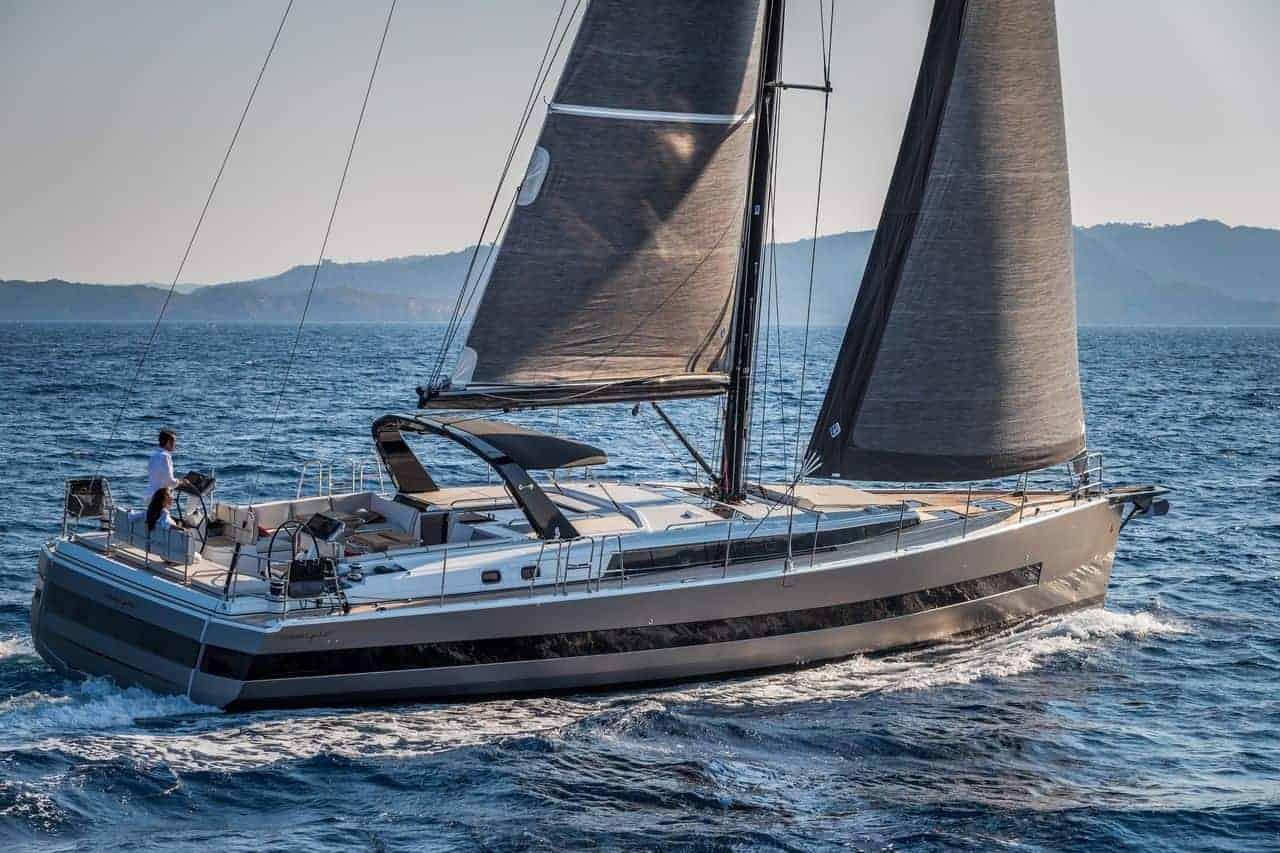 Man sailing the Beneteau Oceanis Yacht 62 along side beautiful coastline