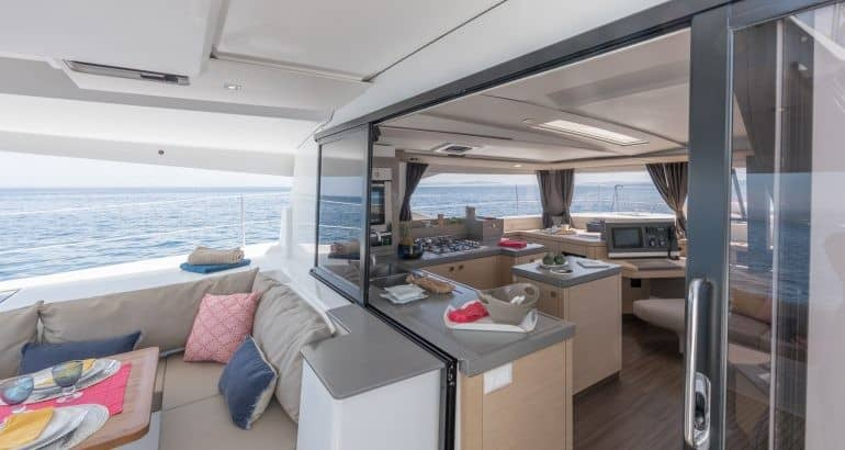 The deck of the Fountaine Pajot Saona 47 with open doors into the saloon, showing the interiors of the spacious yacht