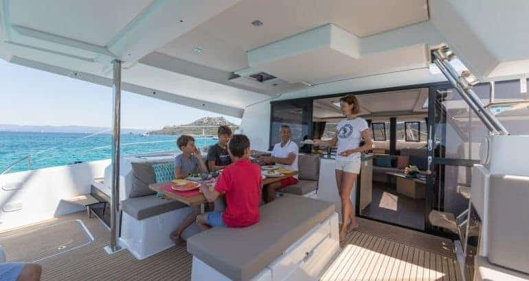 A family of five enjoying dinner on the deck of a Fountaine Pajot Saona 47 a beautiful sunny day