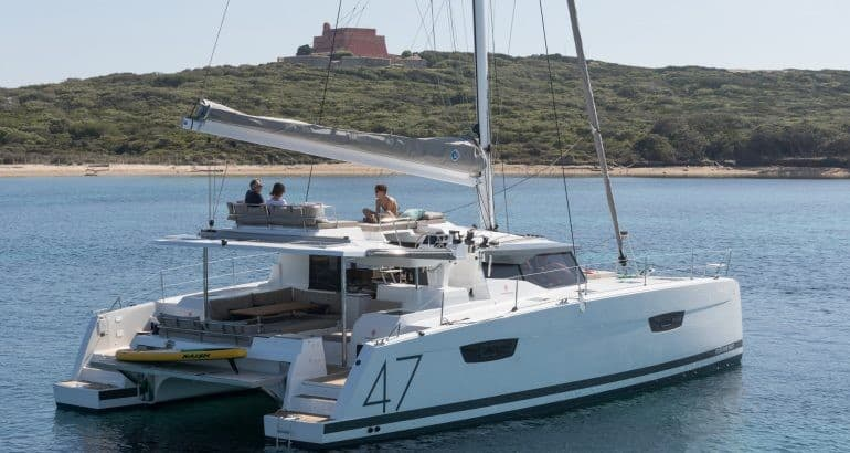 The Fountaine Pajot Saona 47 floating close to a shoreline while three persons chill on the flybridge