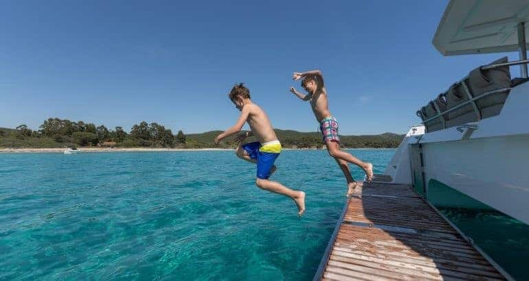 Two young boys jumping down to the crystal clear water from Fountaine Pajot Saona 47