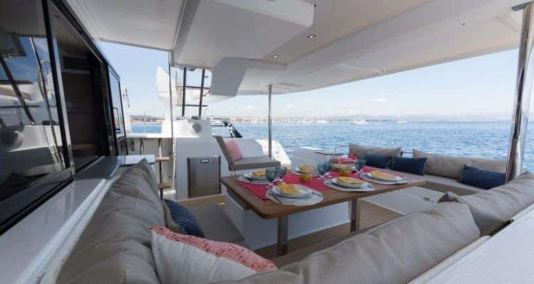 Set table on the deck of a Fountaine Pajot catamaran during a beautiful, sunny day