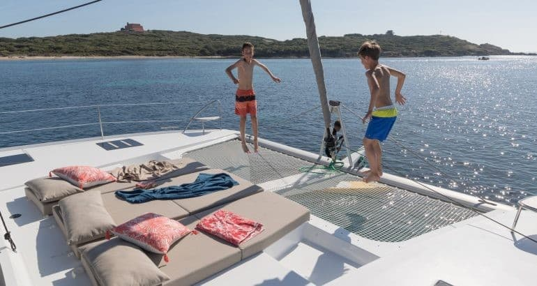 Two boys jumping on the trampolines on the front deck of a Fountaine Pajot Saona 47