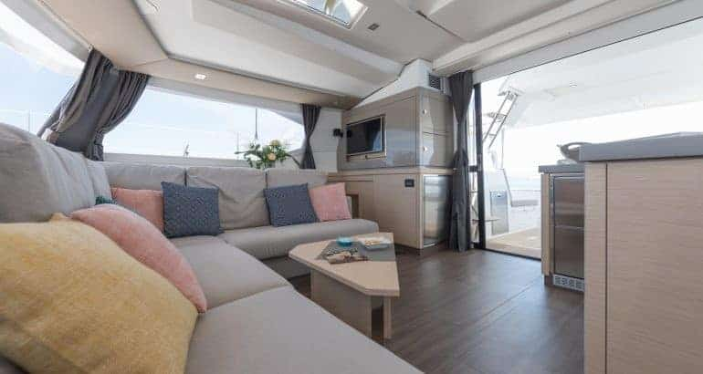 A corner couch in the saloon of a Fountaine Pajot Saona 47