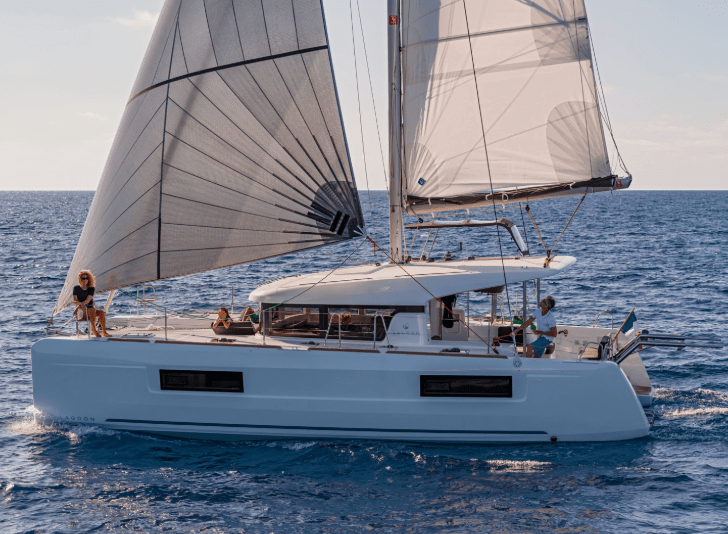 Family posing on the Lagoon 40 while its sailing the seas with wind in its sails