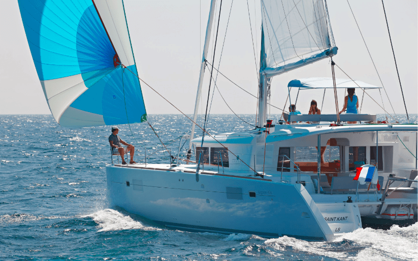Lagoon 450 F in actin with wind in its sail while a man relaxes on deck and three other persons are at the flybridge