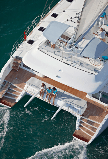 Lagoon 620 from above with a happy family sitting on the transom