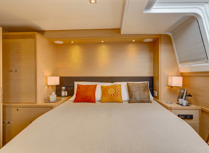 Cozy wood interior and king size bed in a cabin of Lagoon 620