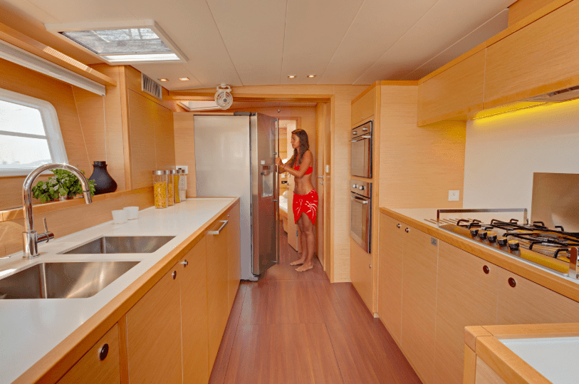 Girl at the refrigerator in the galley of a Lagoon 620