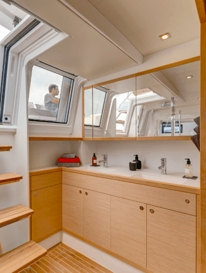 Soothing design in the head of the Lagoon 620 with stairs heading up to deck