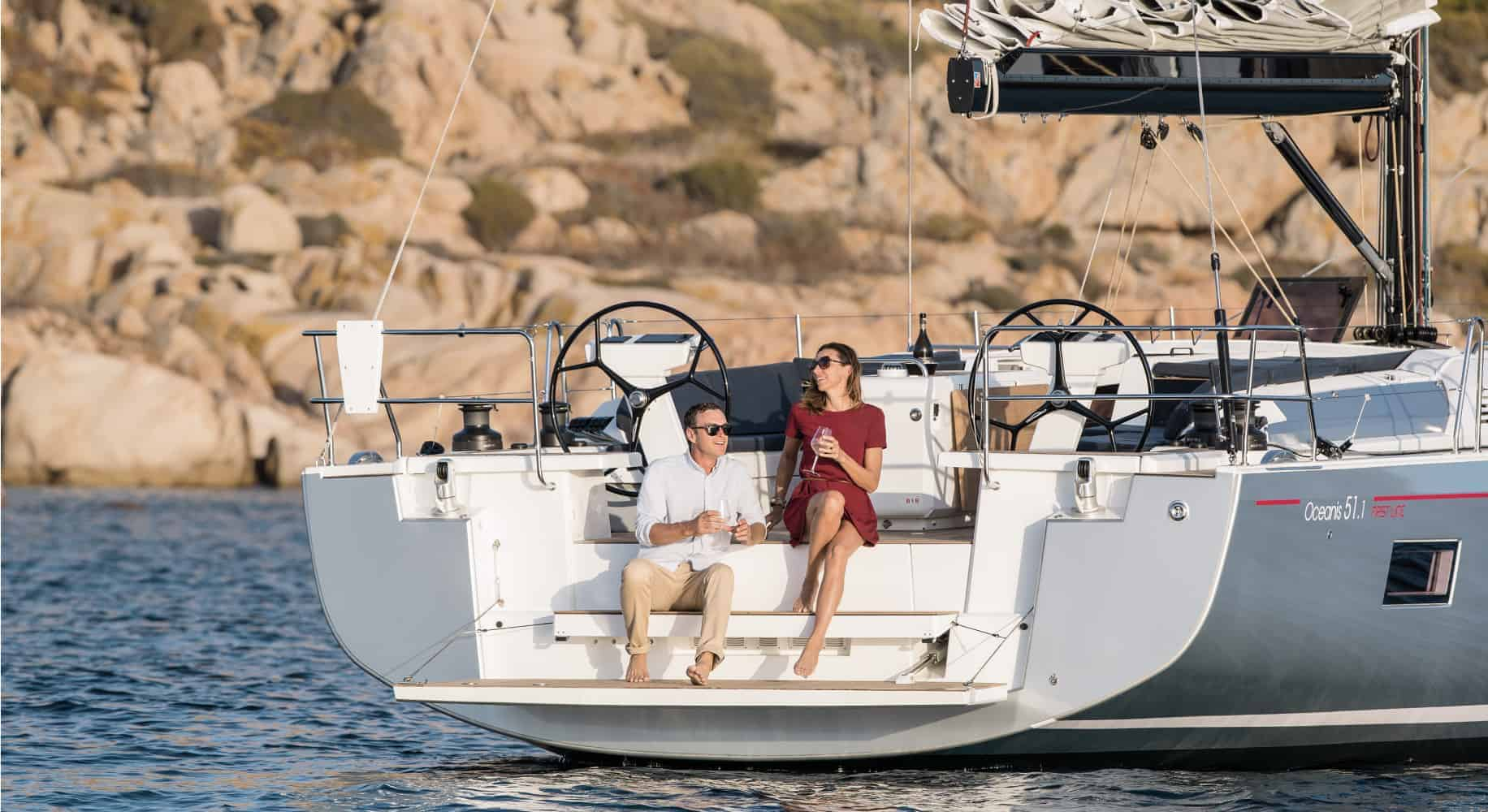 Couple relaxing while enjoying a drink togheter at the stern of the Beneteau Oceanis 51.1