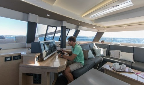 A man sitting at the navigational area of the elegantFountaine Pajot SABA 50