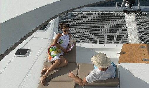 Man and woman lies on loungers on the front deck of a Fountaine Pajot SABA 50