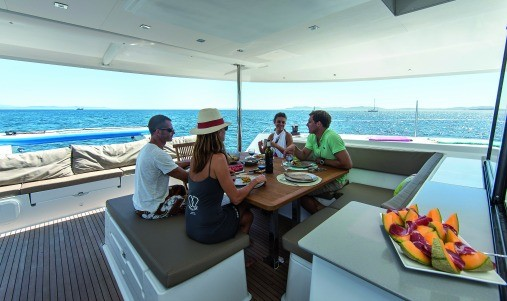 People sitting at the dinner table on the deck of a Fountaine Pajot SABA 50 eating fruits