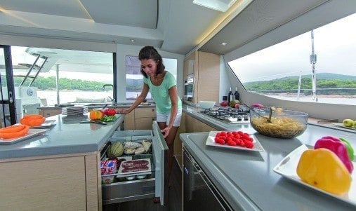 Woman in the neatly designed galley of a Fountaine Pajot SABA 50 with lots of colourful fruits and vegetables