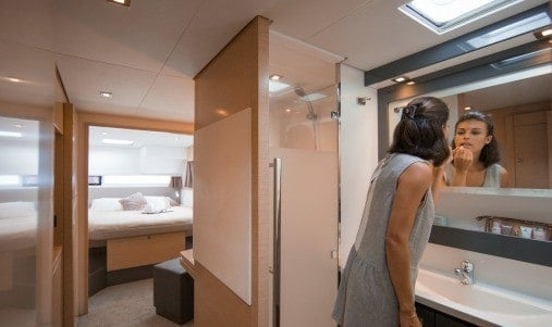 Woman putting lipstick on in a hallway in one of the hulls of the Fountaine Pajot SABA 50
