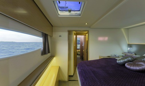 Cabin in one of the hulls of the Fountaine Pajot SABA 50 with a big, made bed with purple sheets