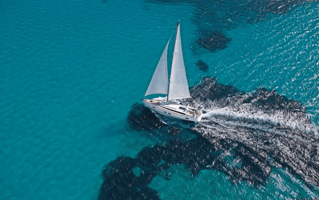 Beneteau Oceanis 55.1 cruising through crystal clear still water