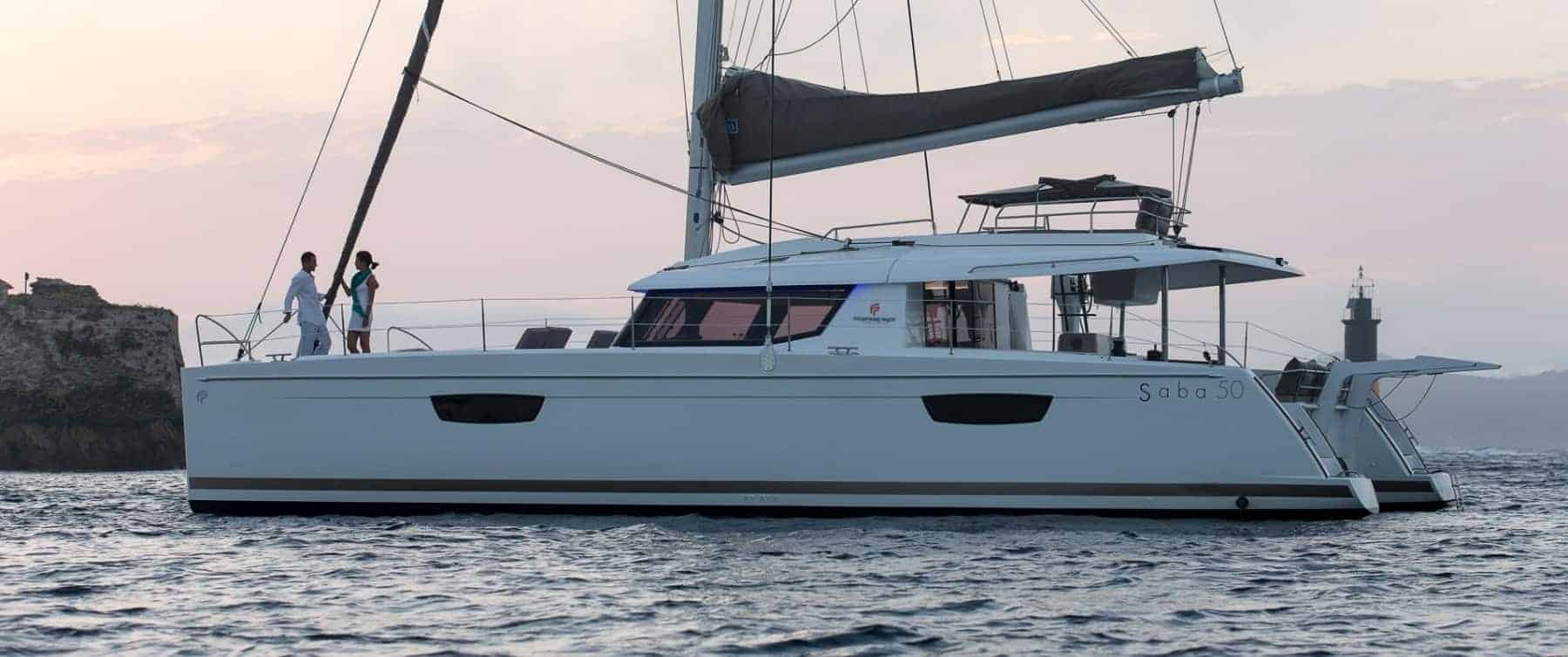 Fountaine Pajot SABA 50​ floating in calm water an evening and a man and a woman is having a conversation on deck