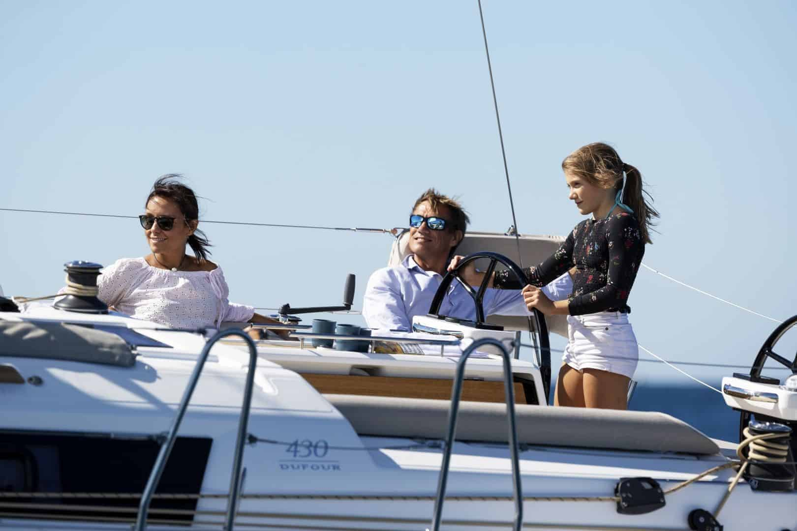 Man, woman and a young girl and the cockpit of the Dufour Grand Large 430 enjoying themselves with the girl at the steering wheel