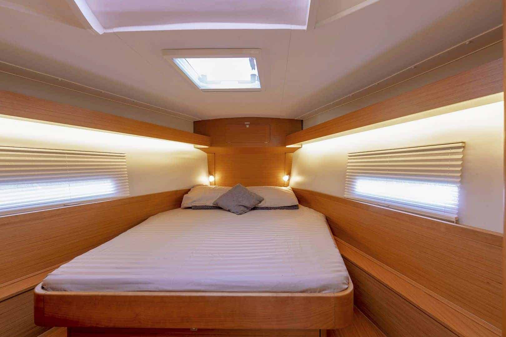 Soothing cabin with a nice bed in it with windows on both sides and in the ceiling above the bed