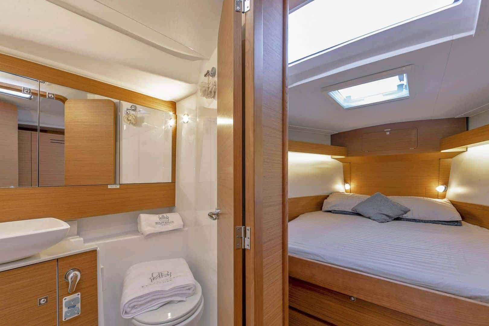 Head of the Dufour Grand Large 430 with towels on the toilette and the cabin is to the right in the next room
