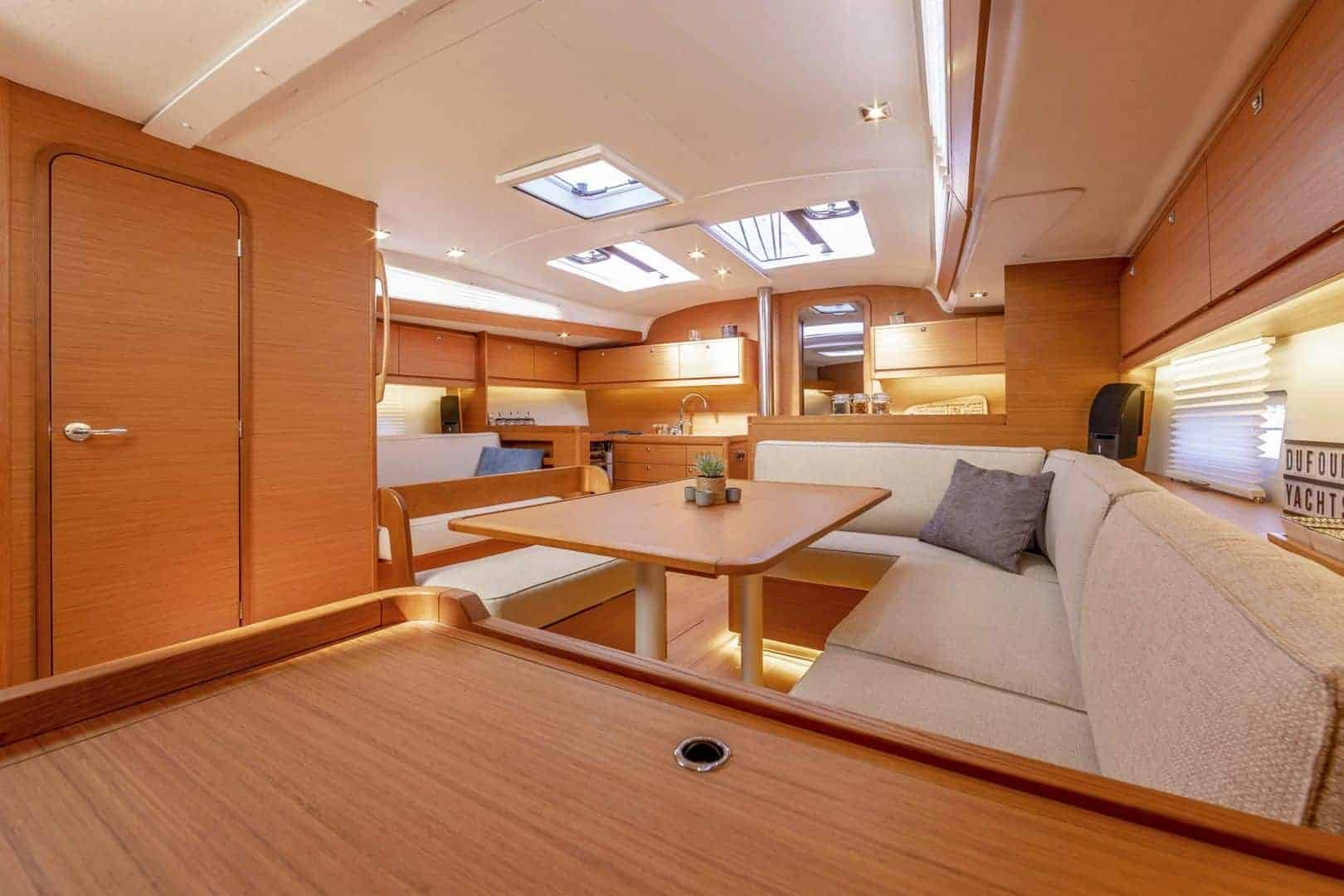 Overview of the beautiful and wooden interior of the Dufour GL 430 with saloon and galley