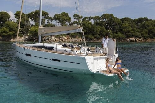 Dufour GL 460 docked close to an amazing coastline on a sunny day with two girls sitting on the transom of the yacht bathing their feet