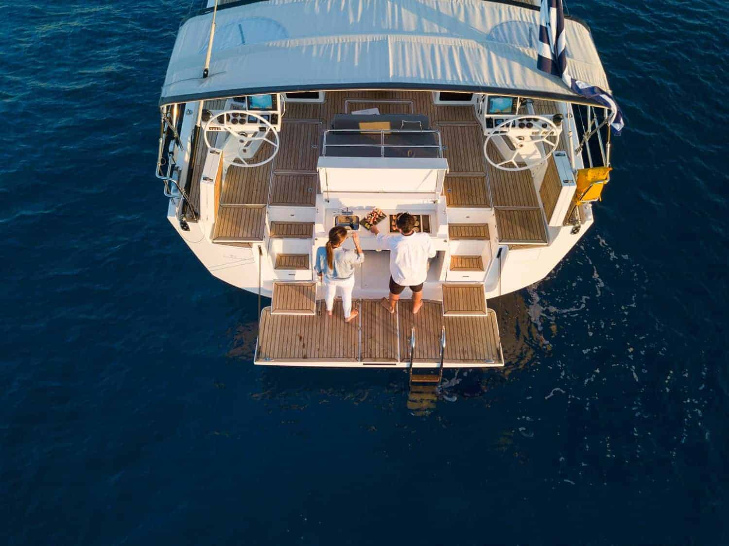 Couple enjoying a appetizer togheter on the luxurious and minimalistic rear of the Dufour Exclusive 63