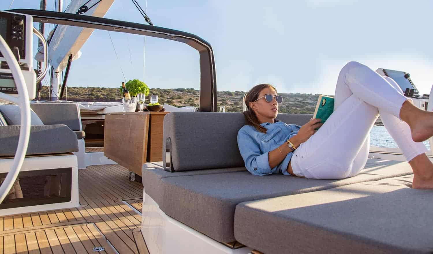 Woman relaxing while reading a book on the massive and luxurious cockpit of the Dufour Exclusive 63