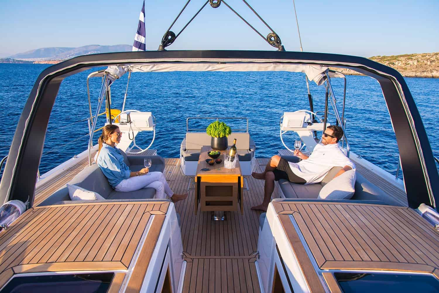 Couple having a romantic moment on the beautiful cockpit area of the Dufour Exclusive 63