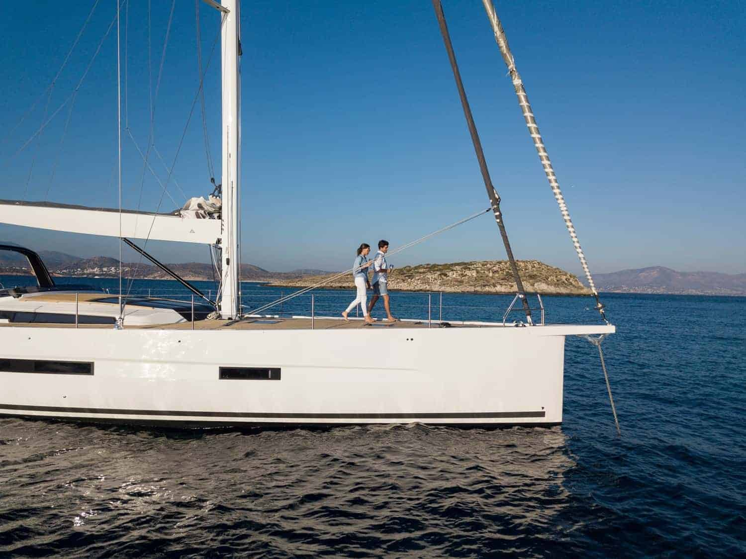 Couple taking a walk on the massive deck area of the Dufour Exclusive 63