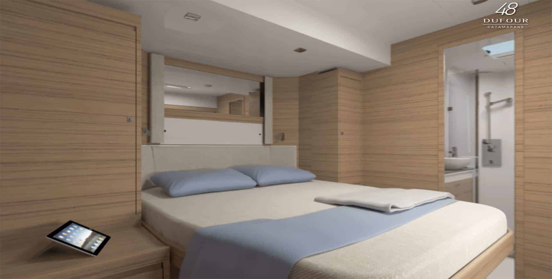 Made, cozy bed in a cabin of the Dufour Catamaran 48 with a tablet on the bedside table