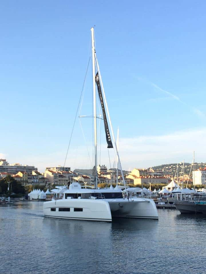 Dufour Catamaran 48 cruising in a marina of a beautiful town seen in the background