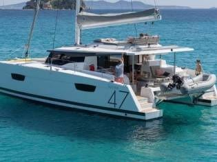 Fountaine Pajot Saona 47 from behind, floating in a tropical sea with some cliffs in the background