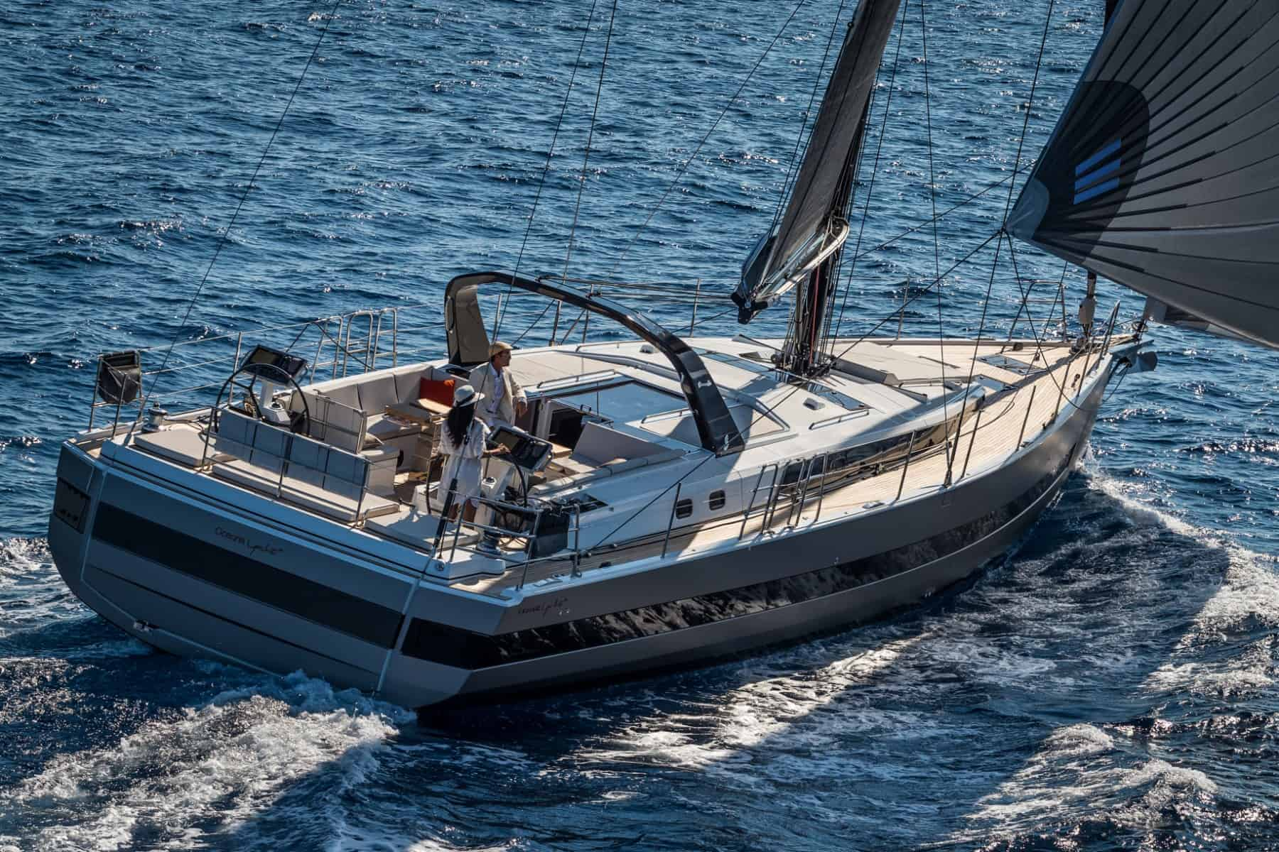 Couple sailing the Beneteau Oceanis Yacht 62 through the splashing waves