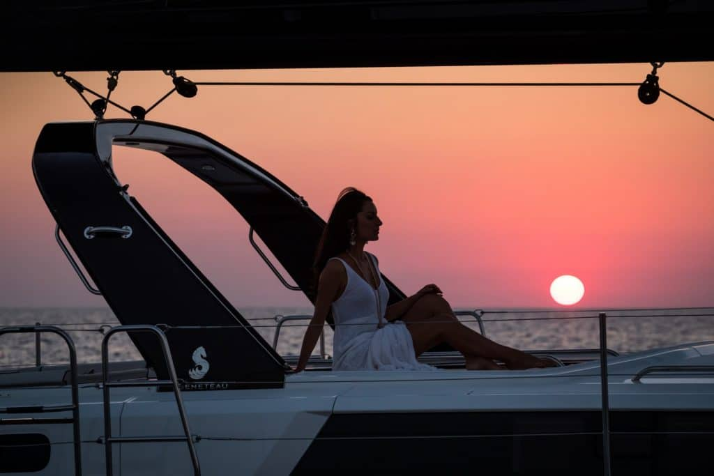 Woman enjoying amazing sunset at the massive front deck of the Beneteau Oceanis Yacht 62