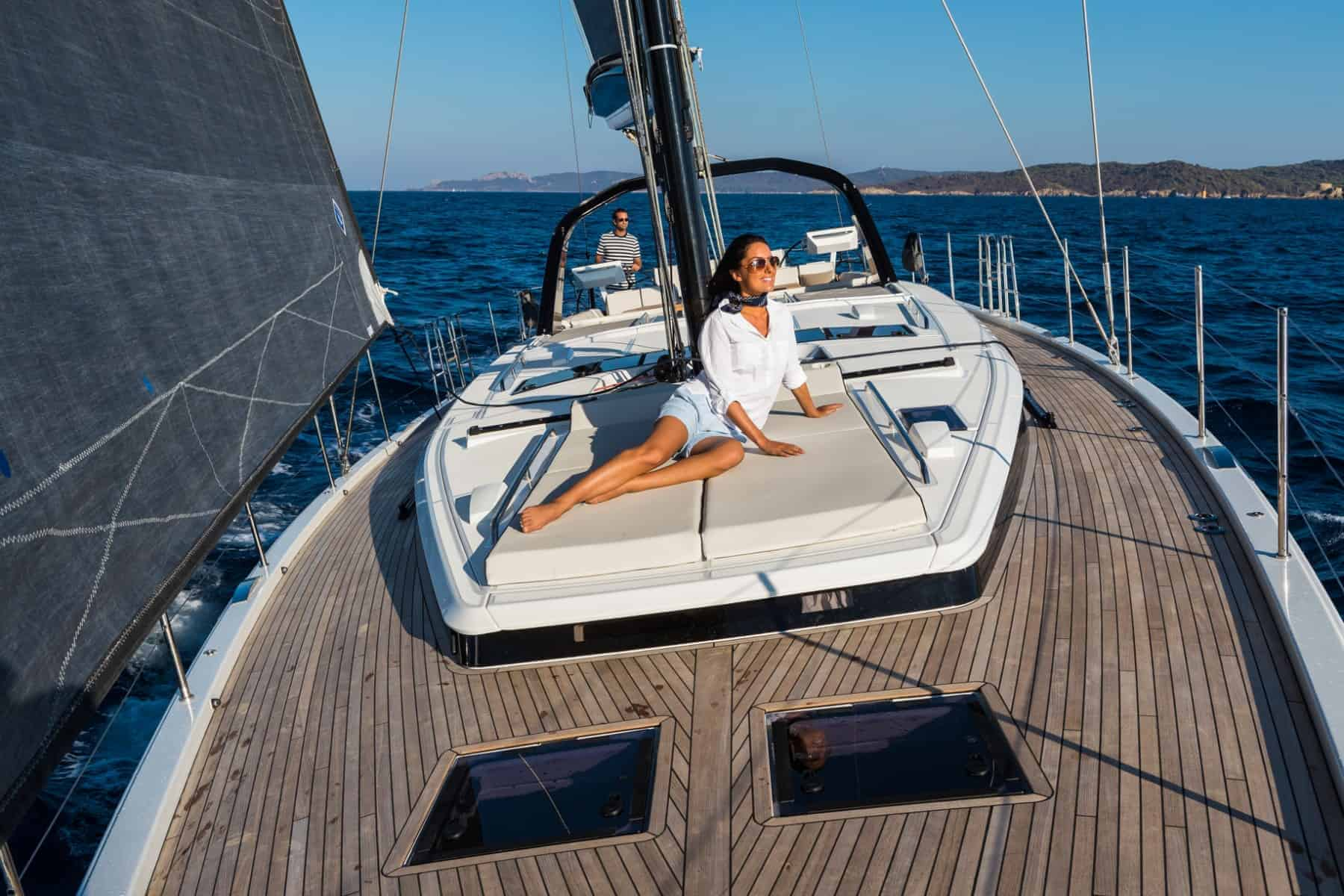 Woman enjoying the refreshing wind breezes at the massive front deck of the Beneteau Oceanis Yacht 62