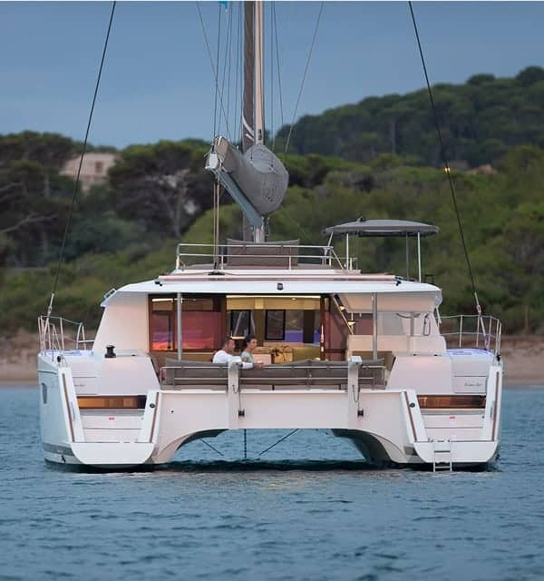 The Fountaine Pajot SABA 50 docked close to a shoreline while a couple enjoying their time together on deck