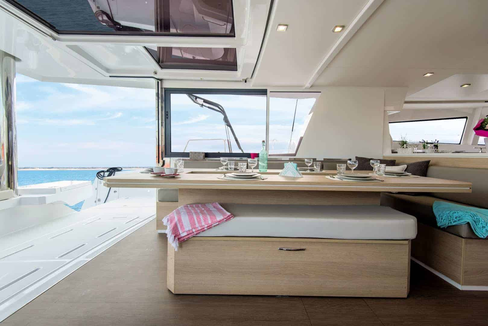 Set table and blankets lying on the sofas of the delightful deck of the Bali 5.4