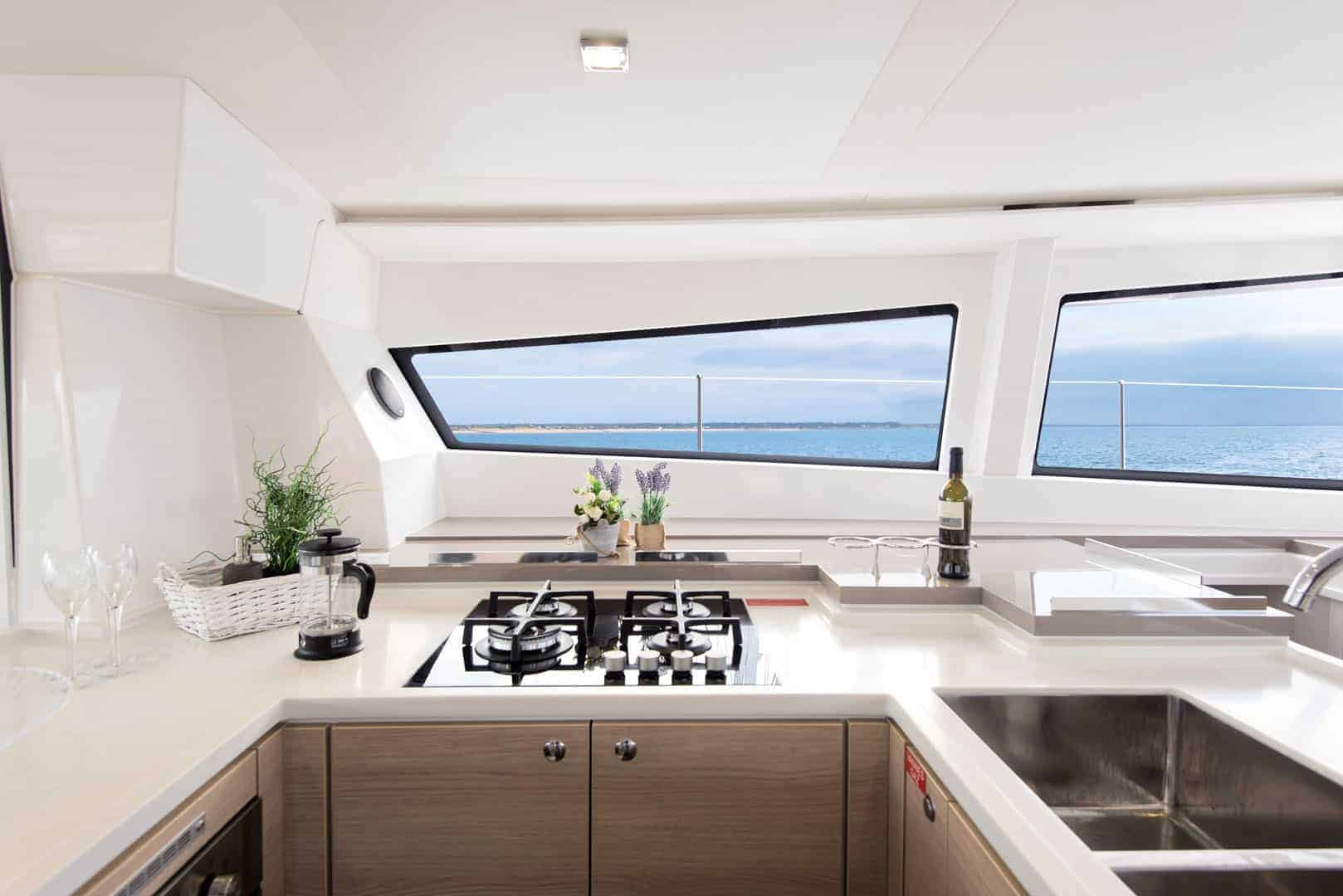The galley of the Bali 5.4 with elegant design on everything from the windows, sink and stove, to the practical built-in bottle holders