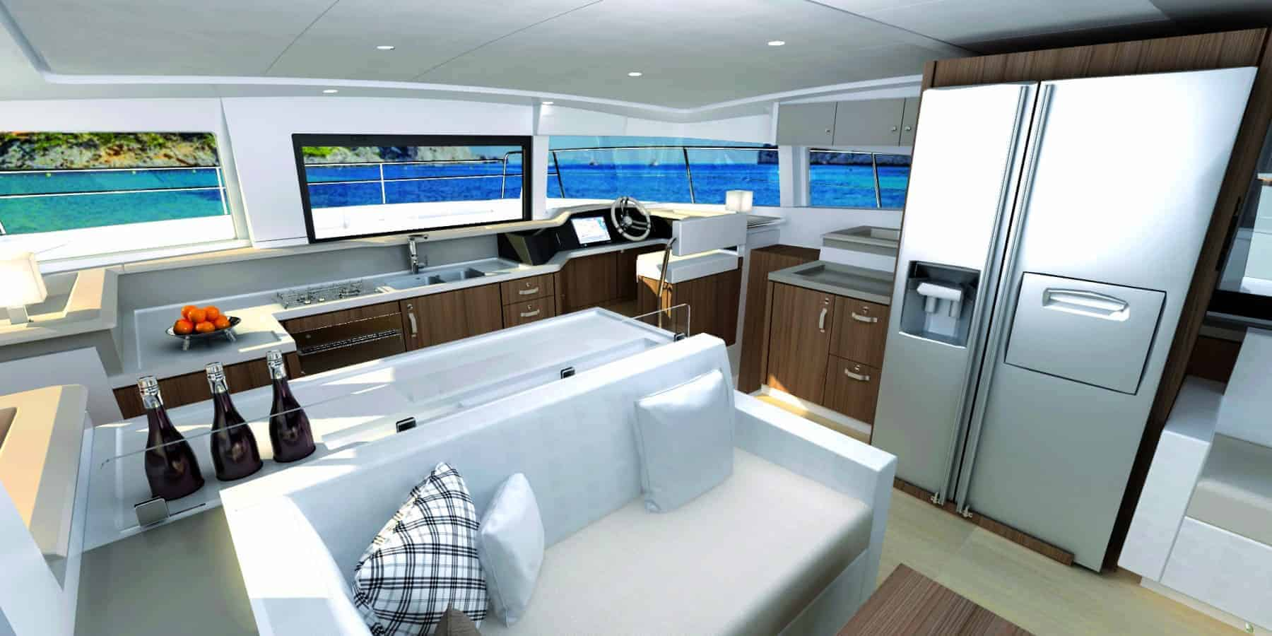 Beautiful layout of the Bali 4.3 MY Revolutionary's saloon with a white sofa and the galley behind it with fridge and freezer with built-in minibar and ice machine