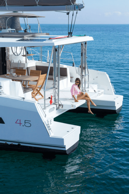 Rear of an anchored Bali 4.5 with a woman in pink shirt sitting on the transom