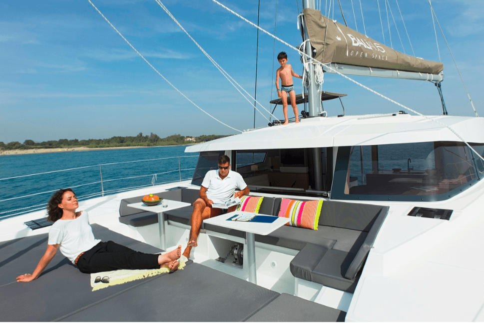 Man and woman relaxing on deck of a Bali 4.5 while a kid plays on the roof